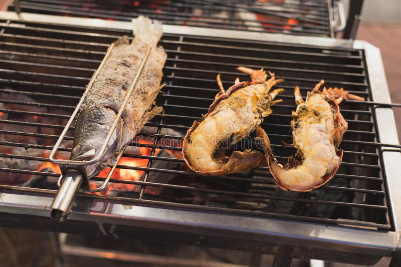 Grilled fish and lobsters lying on the charcoal grill over the red embers - street food in Bangkok royalty free stock images