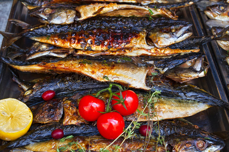 Grilled fish mackerel being served on food stall on open kitchen international food festival event of street food.  royalty free stock image