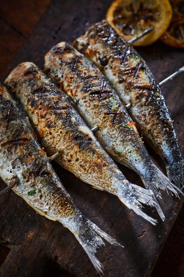 Grilled fish on metal skewers in close-up royalty free stock images