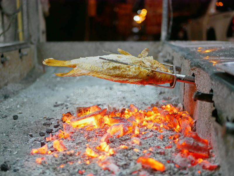 Grilled fish, Red Tilapia, Plaa Tubtim, Pla Pao, and red burning charcoals in a big stove royalty free stock photos
