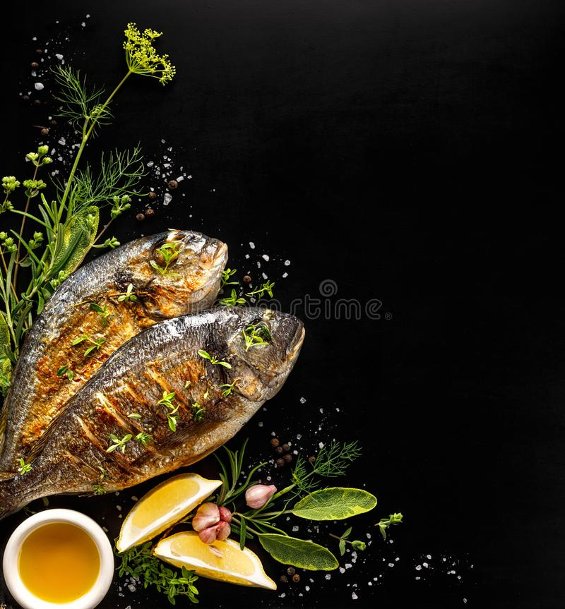 Grilled fish, sea bream with additions, herbs, olive oil, spices on a black background. Composition in the bottom left corner royalty free stock photography