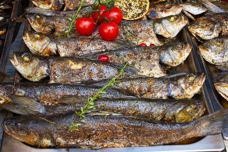 Grilled fish seabass being served on food stall on open kitchen international food festival event of street food. Grilled fish sea bass being served on food stock photos