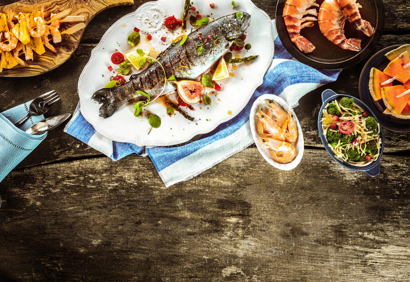 Grilled Fish and Seafood Dishes on Wood Table royalty free stock photo