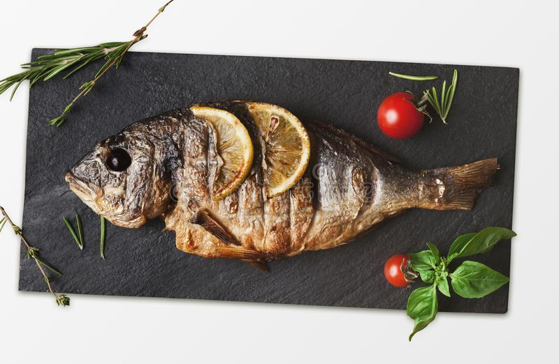 Whole grilled dorado on slate,. Grilled fish on slate on white. Top view of whole roasted dorado, cutout for menu stock photography