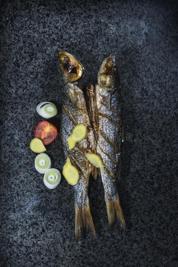 Grilled fish with spices, vegetables and herbs on slate background ready for eating. royalty free stock photo