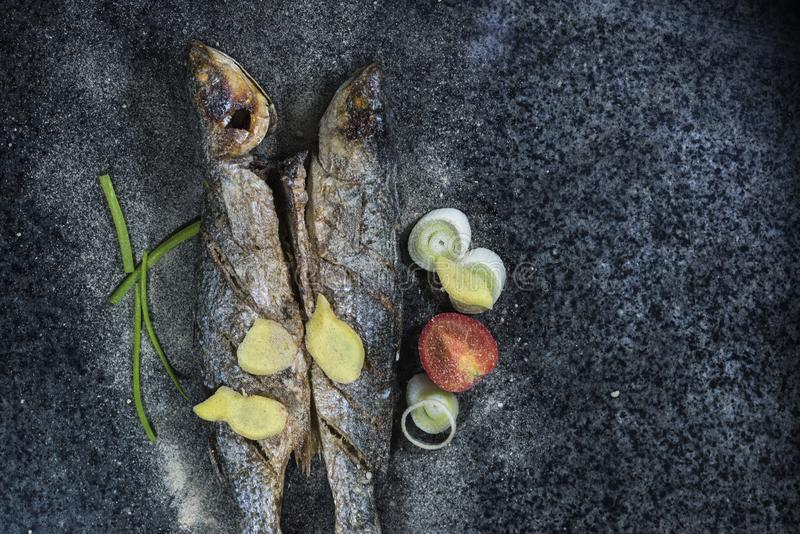 Grilled fish with spices, vegetables and herbs on slate background ready for eating. royalty free stock images