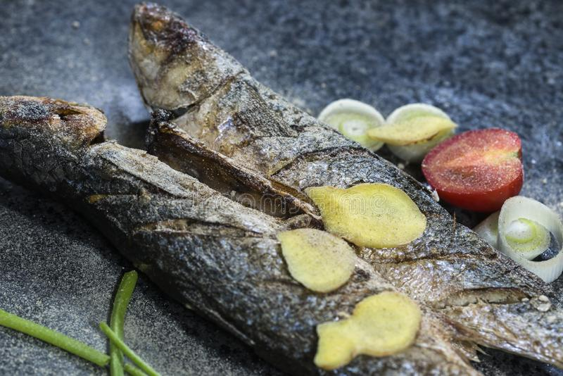 Grilled fish with spices, vegetables and herbs on slate background ready for eating. stock photos