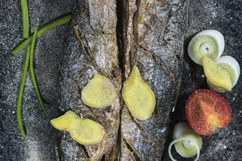 Grilled fish with spices, vegetables and herbs on slate background ready for eating. stock photography
