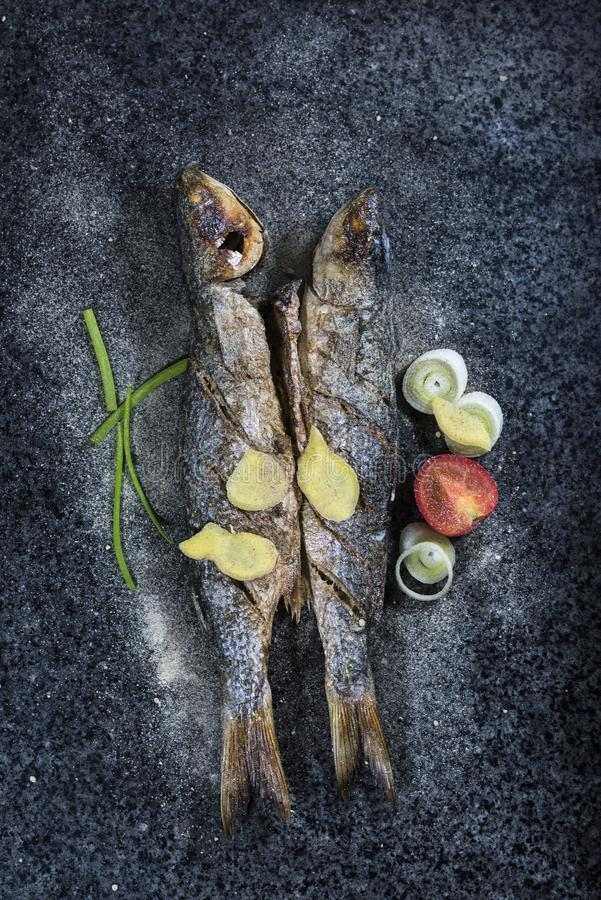 Grilled fish with spices, vegetables and herbs on slate background ready for eating. royalty free stock photos