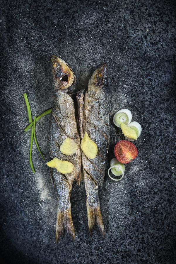 Grilled fish with spices, vegetables and herbs on slate background ready for eating. royalty free stock image