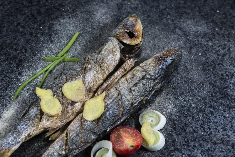 Grilled fish with spices, vegetables and herbs on slate background ready for eating. stock photo