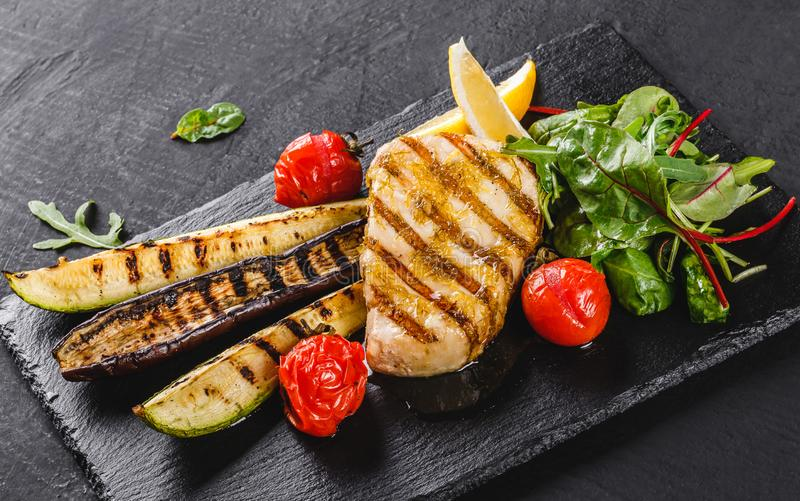 Grilled fish steak garnished with salad of spinach and grilled vegetables on shale background over dark background. Hot fish dish.  royalty free stock photo