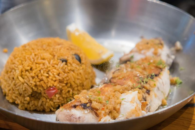 Grilled fish steak served with fried rice and lemon in a deep pan placed. On a wooden board royalty free stock image