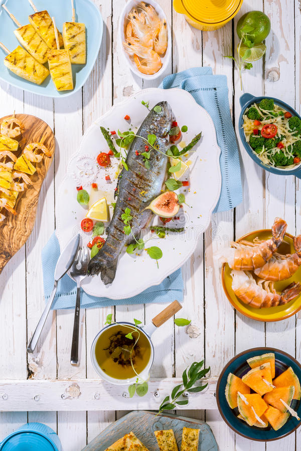 Grilled Fish on Table with Other Dishes stock images