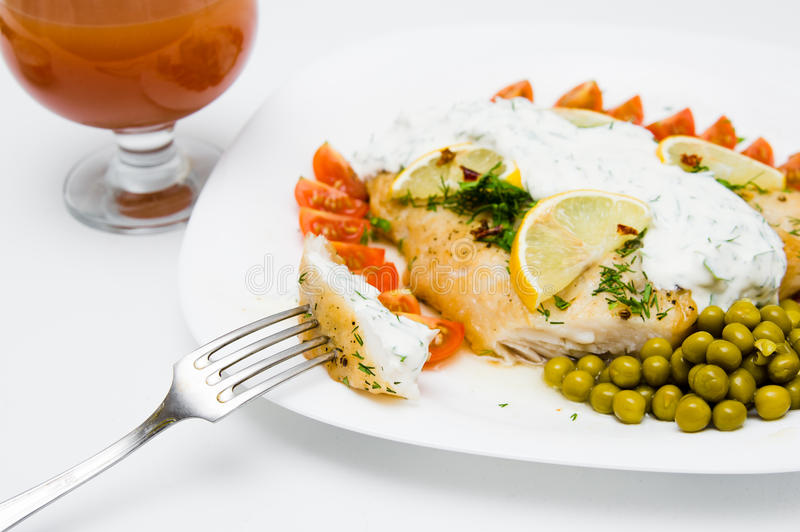 Grilled fish with vegetables and cream sauce stock image