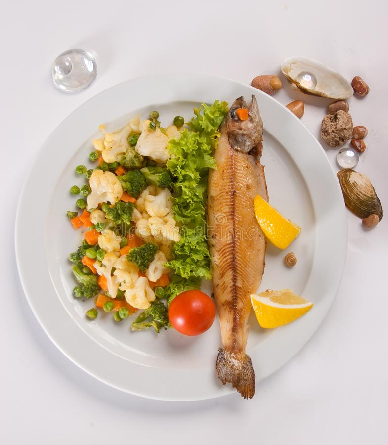 Grilled fish with vegetables ona white background. Decorated, food, dinner, meal, seafood, lunch, roasted, dish, fillet, plate, cooked, dining, lemon, cuisine stock images