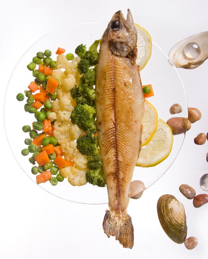Grilled fish with vegetables ona white background. Decorated, food, dinner, meal, seafood, lunch, roasted, dish, fillet, plate, cooked, dining, lemon, cuisine stock photos