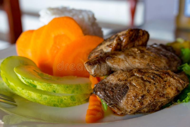 Grilled fish with white rice and fresh vegetables. Asian cuisine concept. Grilled salmon steak with cucumber slices and carrot. royalty free stock image