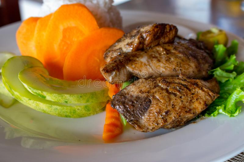 Grilled fish with white rice and fresh vegetables. Asian cuisine concept. Grilled salmon steak with cucumber slices and carrot. stock photos
