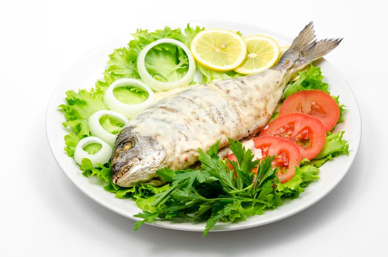 Grilled fish with white sauce on fresh vegetables. stock photos