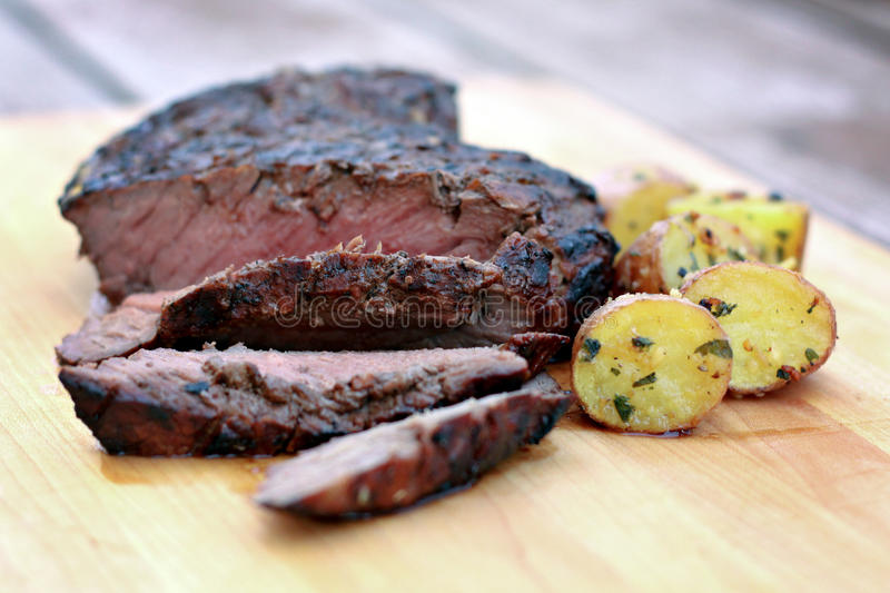 Grilled Flank Steak. With roasted potatoes royalty free stock images