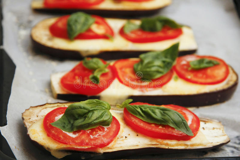 Grilled food and additives with tomatoes basil and eggplant.  royalty free stock image