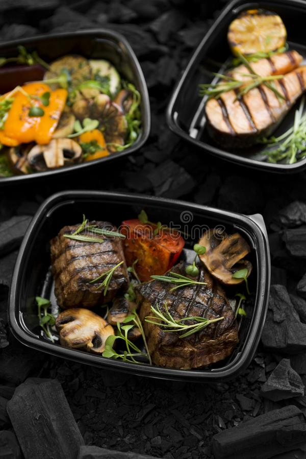 Grilled food in black plastic take away boxes for delivery. On coal background stock image