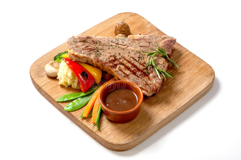 Grilled Foods - BBQ Beef Steak with hot sauce and vegetables on a wooden Board stock photo