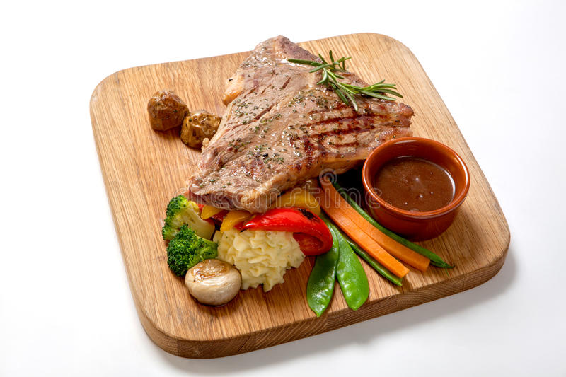 Grilled Foods - BBQ Beef Steak with hot sauce and vegetables on a wooden Board royalty free stock image