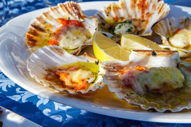 Grilled Fresh Scallop on Shell and lemon on the plate. Horizontal stock photography