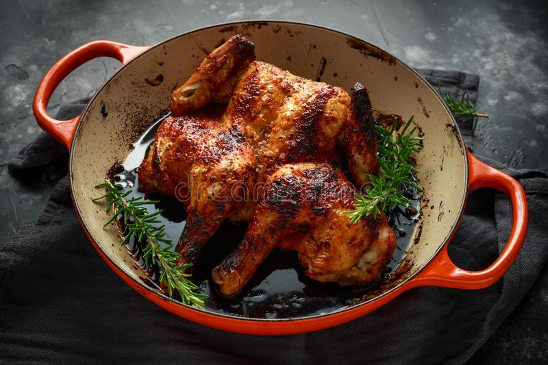 Grilled fried roast Chicken Tabaka in frying pan with rosemary stock photo
