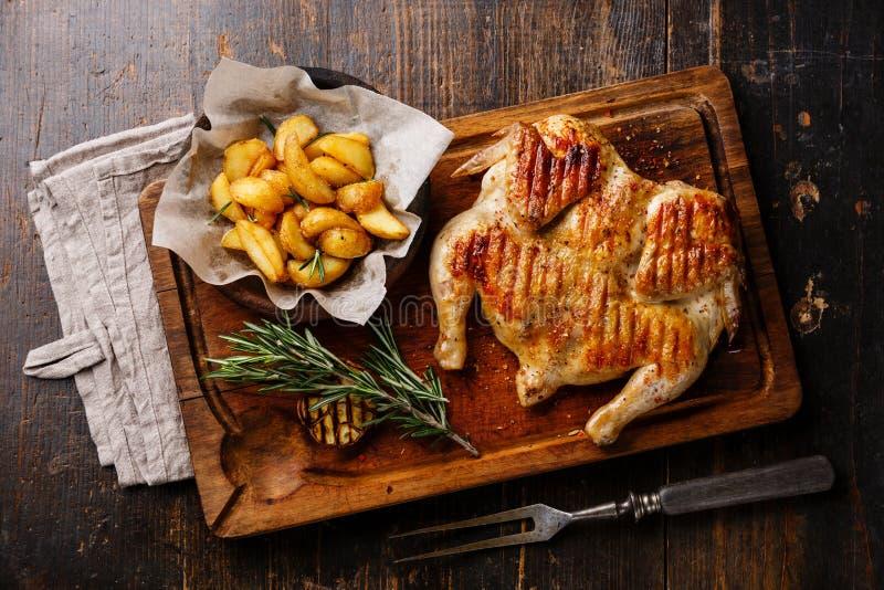 Grilled fritou o frango assado Tabaka e as cunhas da batata fotografia de stock royalty free