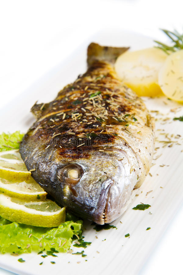 Grilled gilt head sea bream. On plate with lemon and rosemary and potatoes stock photos