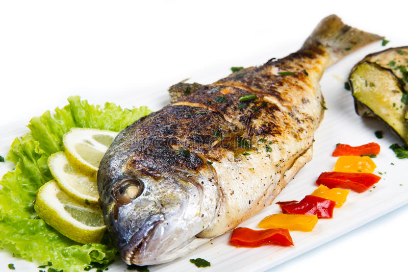 Grilled gilt head sea bream on plate. With lemon ,salad and grilled vegetables stock photos
