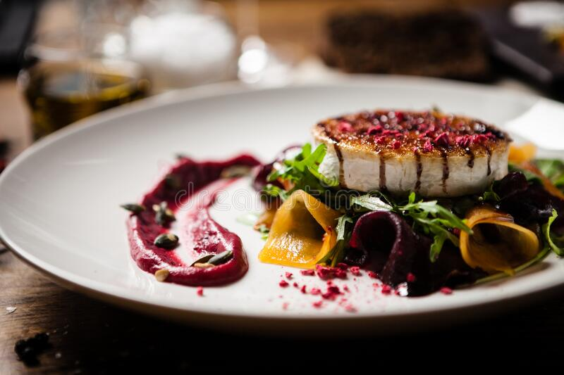 Grilled goat cheese salad served on a plate in restaurant stock photography