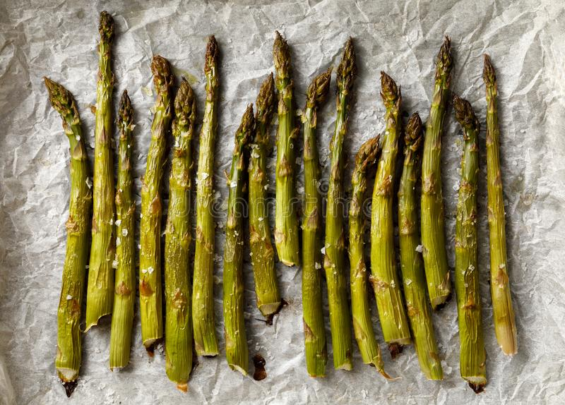 Grilled green asparagus sprinkled with sea salt flakes on white parchment paper, top view stock photos