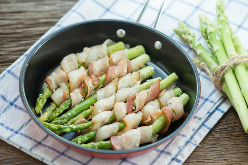 Grilled green asparagus wrapped with bacon in pan. stock photography