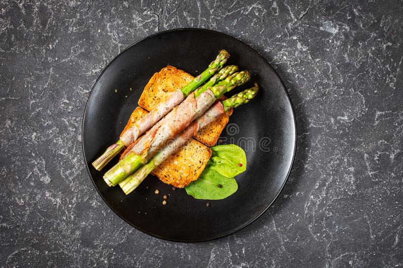 Grilled green asparagus wrapped with bacon on toasts stock photos