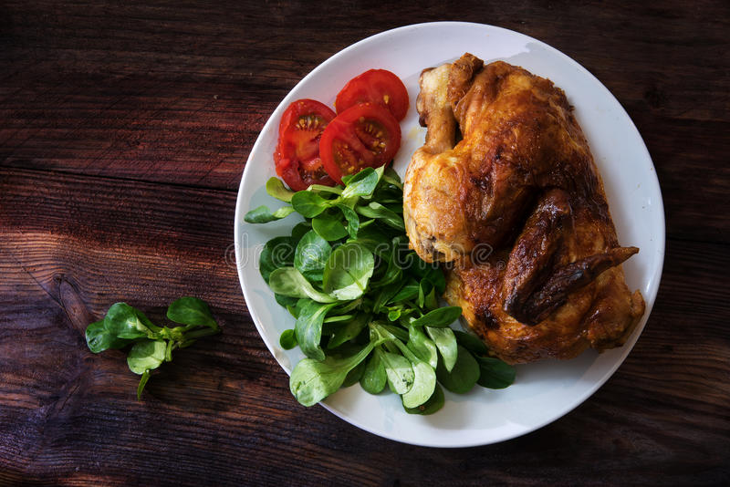 grilled half chicken with tomatoes and corn salad on a white plate on a dark rustic wooden board, top view from above with copy stock image
