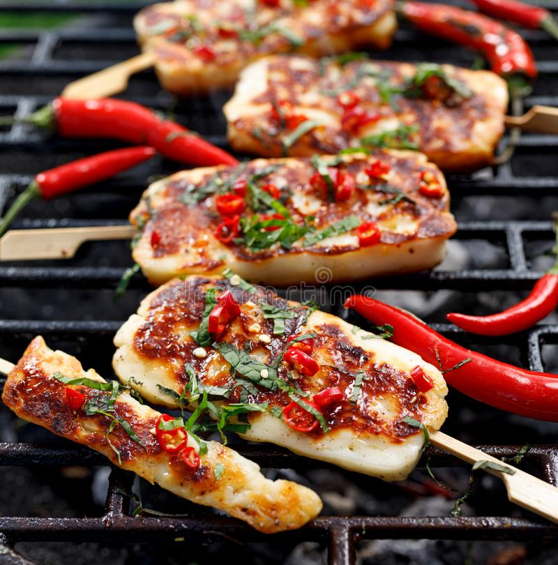 Grilled halloumi cheese with the addition of mint and chilli pepper while grilling outdoors, top view. Grilled halloumi cheese with the addition of mint and royalty free stock images