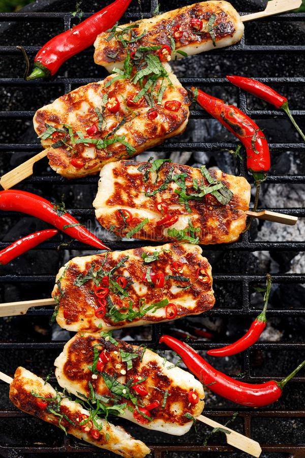Grilled halloumi cheese with the addition of mint and chilli pepper while grilling outdoors, top view. Delicious, vegetarian, grilled snack stock photography
