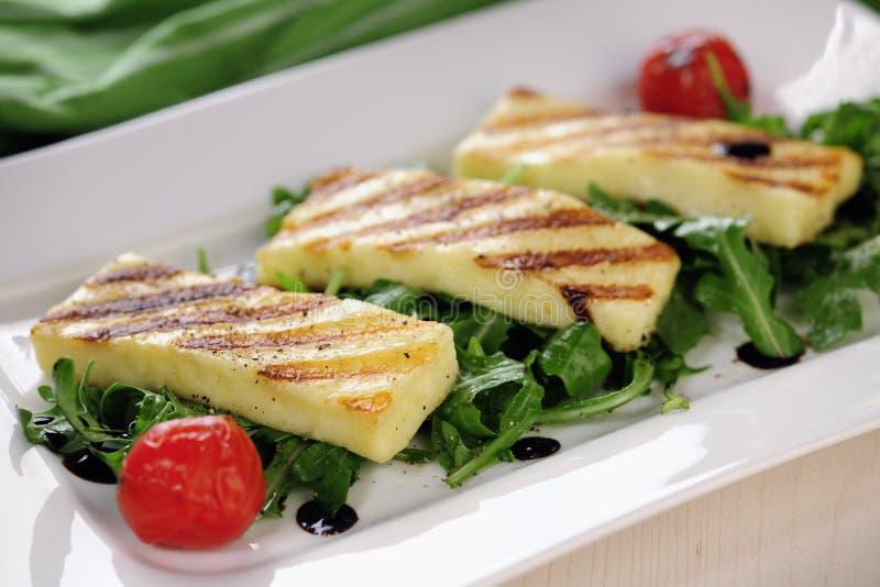 Grilled Halloumi cheese on rocket salad stock photos