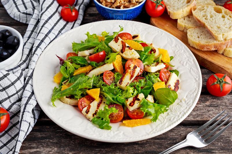 Grilled Halloumi Cheese salad witch orange, tomatoes and lettuce. healthy food.  stock photos