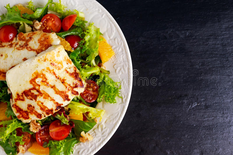 Grilled Halloumi Cheese salad witch orange, tomatoes and lettuce. healthy food.  royalty free stock images