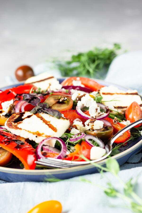 Grilled haloumi halloumi cheese salad witch tomato, baked pepper, micro green and onion on a blue plate. royalty free stock photography