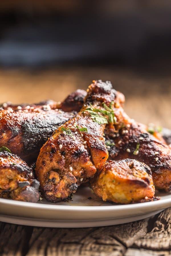 Grilled hicken腿BBQ用香料草本和芝麻在被烘烤的纸 在白色板材的烤禽畜膳食 免版税图库摄影