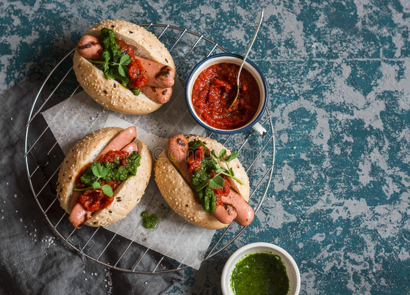 Grilled hot dogs with tomato sauce and chimichurri on wooden background. Top view stock photos