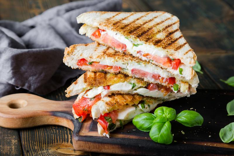 Sandwiches with mozzarella, basil and tomatoes. Italian sandwich. Grilled Italian sausage sandwich with mozzarella and tomatoes royalty free stock photography