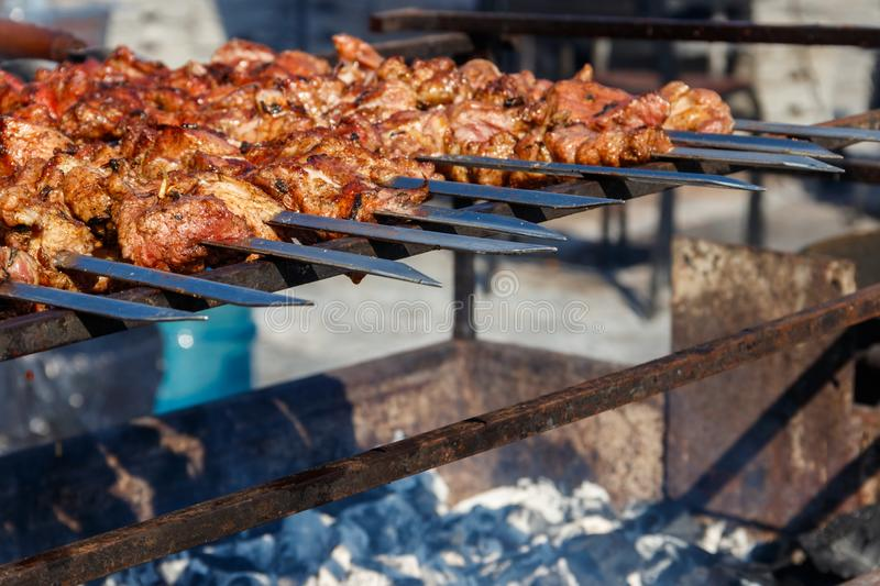 Grilled kebab cooking on metal skewer. Roasted meat cooked at barbecue stock photos