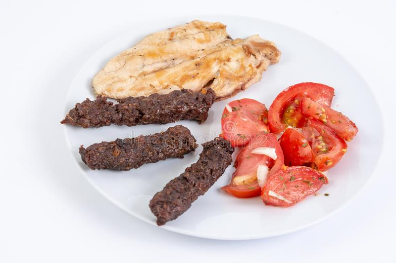 Grilled kebabs and chicken meat served with fresh tomato salad royalty free stock image